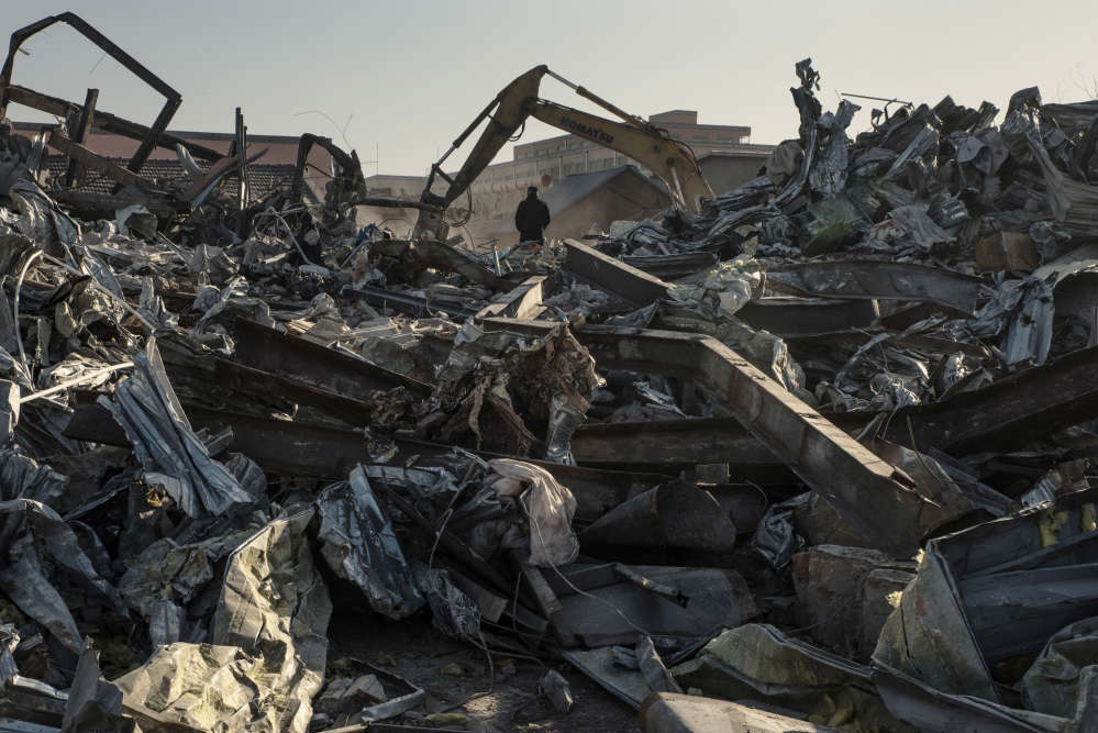 Un homme regarde les bulldozers au travail dans les ruines d'ateliers et de résidences de Xinjian.
