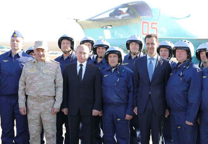 Le ministre de la défense russe et les présidents russe et syrien aux côtés de militaires sur la base de Latakia en Syrie, le 11 décembre.