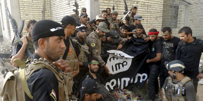 Des soldats irakiens posent avec un drapeau de l'Etat islamique pris aux terroristes à l'universitré d'Anbar, en juillet 2015.