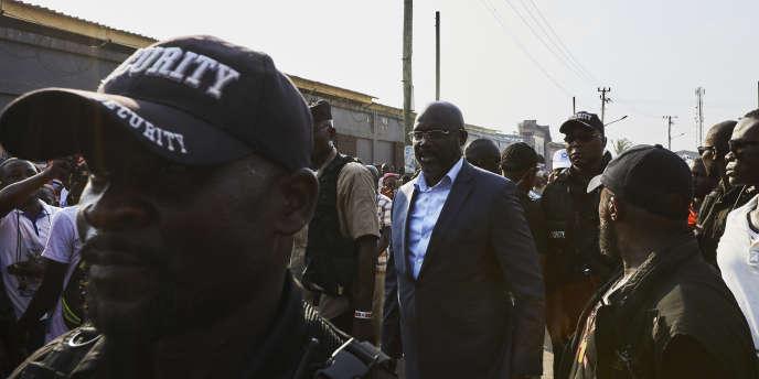 Le candidat à l'élection présidentielle George Weah (en costume), à Monrovia, au Liberia, le 6décembre 2017.