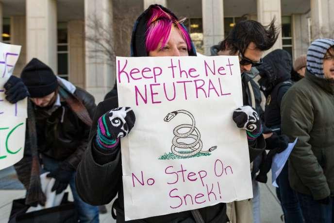 Une manifestante brandit un signe demandant de garder la neutralité du Net, le13décembre, à Washington.