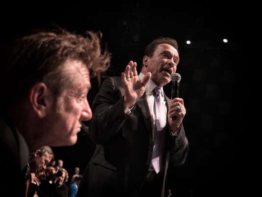 """L'acteur et homme politique américain Arnold Schwarzenegger prend la parole, le 12 décembre 2017, à la Seine Musicale sur l'île Seguin à Boulogne-Billancourt, lors de la séance plénière du """"One Planet Summit"""", devant l'acteur Sean Penn."""