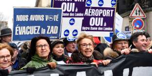 """People hold placards reading """"Yes to the airport"""" during a demonstration in support of the controversial Notre-Dame-des-Landes airport project, on December 13, 2017 in Paris. / AFP / Bertrand GUAY"""