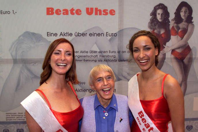 Beate Rotermund-Uhse (au centre), à Francfort, en 1999, devant une reproduction d'une action du groupe qu'elle avait fondé et qui était coté en Bourse.