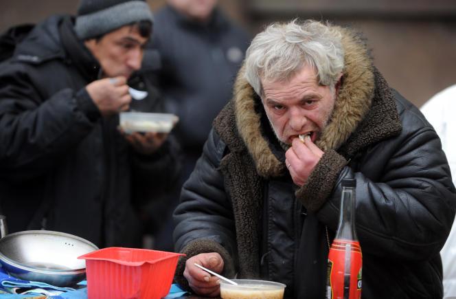 Des sans-abri russes mangent un repas distribué par une association locale, à Moscou, en décembre 2009.