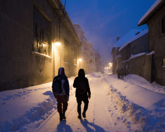 """Deux jeunes migrants marchent dans Briançon pour rejoindre """"Chez Marcel"""", un lieu d'hébergement alternatif pour migrants."""