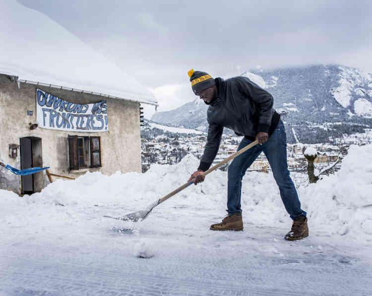 """Justin déblaie la neige devant """"Chez Marcel"""", un lieu d'accueil alternatif pour migrants."""