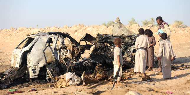 Des habitants inspectent l'épave d'une voiture visée par la frappe d'un drone près de la ville de Marib, au Yémen, le 3 novembre.