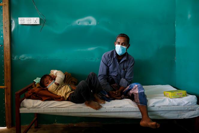 Un père et son enfant atteint de diphtérie dans une clinique gérée par Médecins sans frontières, le 18 décembre à Cox's Bazar, au Bangladesh.