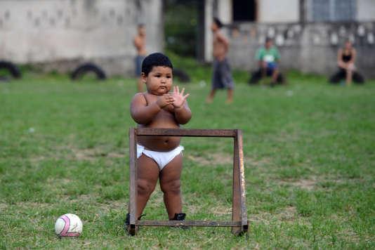Un petit garçon regardedes grands jouer au football au Honduras