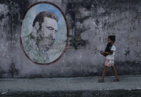 Une petite fille passant devant une peinture murale de Fidel Castro (1926-2016), à Cuba, le 5 février 1998.