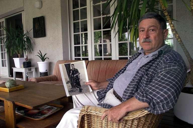 Noël Favrelière, le 5 juin 2001 à Aigrefeuille-d'Aunis, tenant une photo le montrant avec l'uniforme de l'armée française.