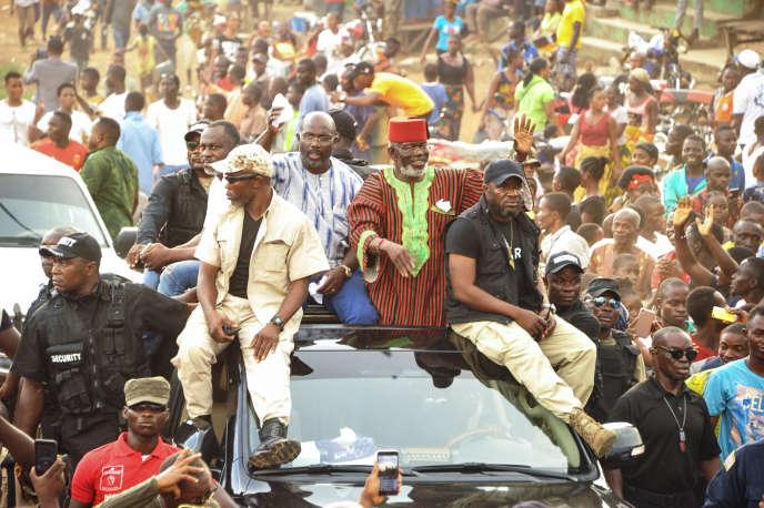 L'ancien chef de guerre Prince Johnson (R) saluant ses partisans sur le toit d'une voiture avec le candidat présidentiel libérien George Weah, qu'il avait approuvé , à Monrovia, le 27 octobre à Monrovia.