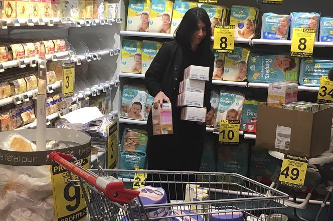 Une pharmacienne retire de la vente des aliments pour bébé, à Paris, le 21 décembre.