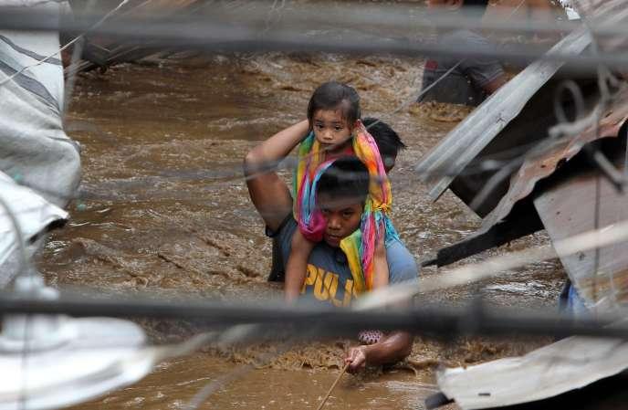Un officier de police porte un enfant dans les rues innondées de Cagayan City, aux Philippines, le 22décembre.
