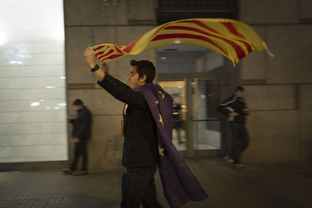 Un jeune militant laisse flotter le drapeau catalan dans les rues de Barcelone, le soir du 21décembre.