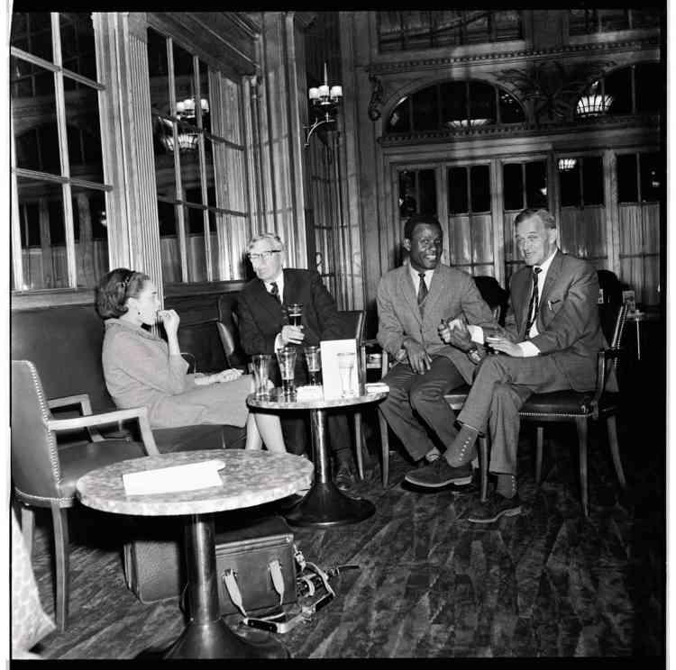 James Barnor entouré de deux journalistes, ainsi que de la secrétaire de la revue Drum, Kayla,qui assistait le photographe. Ils attendent dans hôtel londonien l'arrivée du boxeur Muhammad Ali,récent tombeur de Brian London, en 1966.