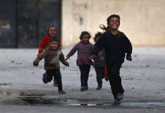 Des enfants s'amusent dans le quartier de la Ghouta, contrôlé par les rebelles syriens dans la ville de Hamouria, en Syrie, le 23 décembre.