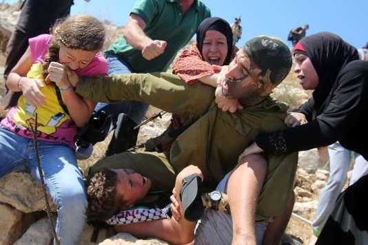 Ahed Tamimi(à gauche) s'oppose, avec d'autres Palestiniens, à l'arrestation d'un enfant, en 2015,.
