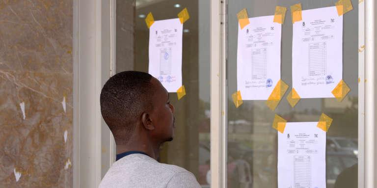 Un agent électoral regarde le décompte des votes affiché sur une fenêtre des locaux de la commission électorale, au stade de Monrovia, au Liberia, le 27décembre 2017.