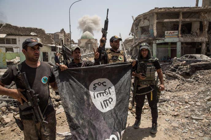 Des soldats célébrent la prise de la mosquée Al-Nouri de Mossoul (Irak), le 2 juillet. Ils ont récupéré un drapeau de l'EI.