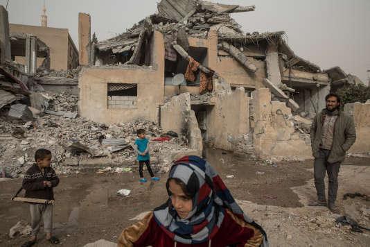 A Tabqa, certains quartiers ont été endommagés par la guerre. Malgré leurs habitations en partie détruites, les civils y vivent encore. Des enfants jouent à la guerre devant une de ces maisons ravagées.