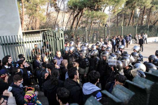 Des étudiants iraniens font face à la police antiémeute, devant l'université de Téhéran, le 30 décembre 2017.