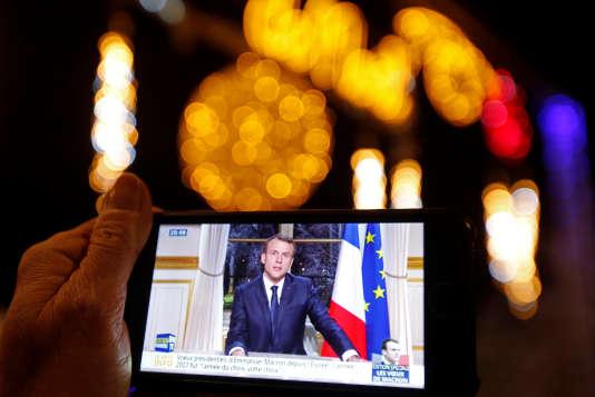 Emmanuel Macron présentant ses vœux depuis le palais présidentiel, sur un écran de téléphone, à Marseille, le 31 décembre.