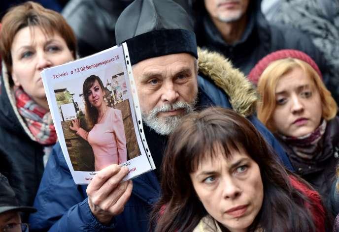Un prêtre orthodoxe tenant une photo d'Iryna Nozdrovska lors d'un rassemblement à sa mémoire, à Kiev le 2 janvier.