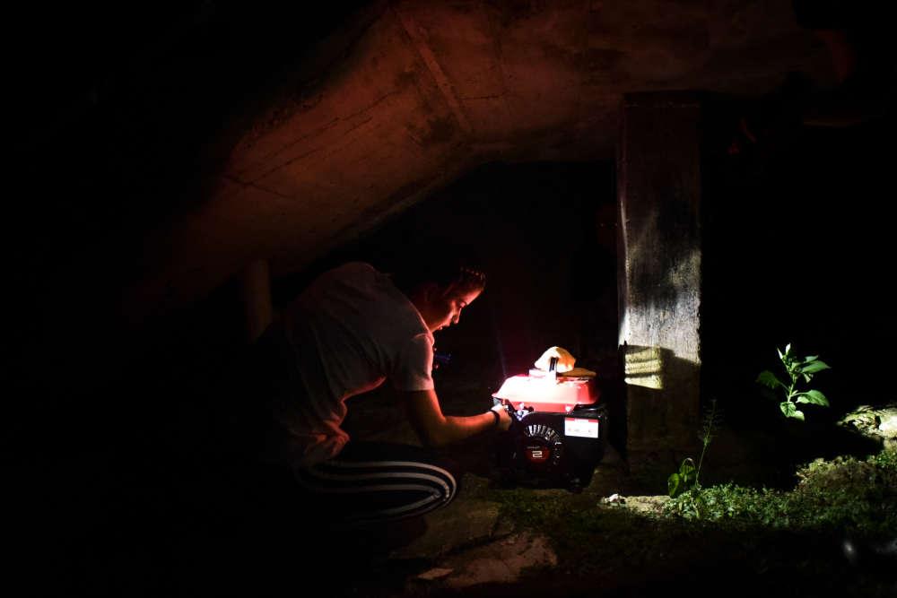 Une habitante met en marche un groupe électrogène, dans le quartier de Patron, le21décembre.