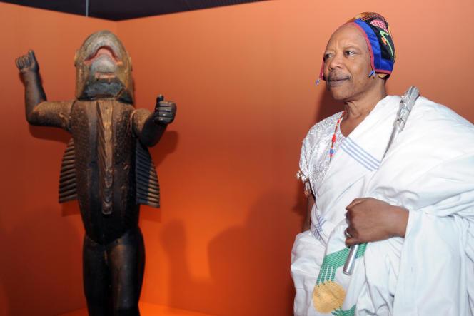 Le roi Behanzin, du Bénin, pose devant la statue de son ancêtre du début du XIXe siècle, lors de sa visite au musée du Quai Branly en 2007.