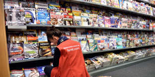 An employee of a newsstand puts magazines on display on February 25, 2015 in Lille. AFP PHOTO /PHILIPPE HUGUEN / AFP PHOTO / PHILIPPE HUGUEN