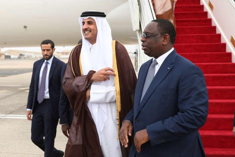 Le président sénégalais Macky Sall accueille l'émir du Qatar, Tamim Ben Hamad Al-Thani, à son arrivée à Dakar, première étape de sa tournée en Afrique de l'Ouest,le 20 décembre 2017.