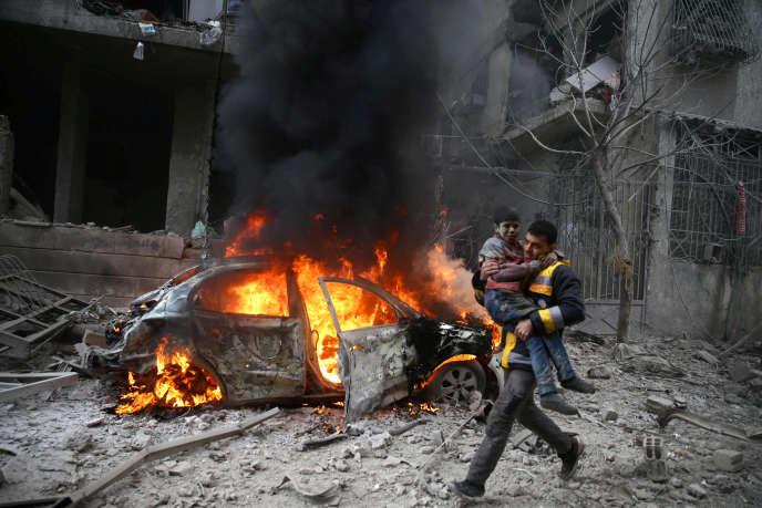 Un membre de la défense civile syrienne porte secours à un enfant blessé à Hamoria, sur la Ghouta orientale, le 6 janvier.