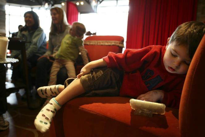Un enfant de trois ans regarde une video sur un téléphone, dans un café à Seattle (Etat de Washington), en 2010.