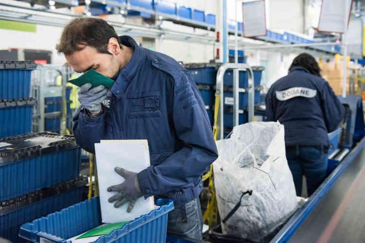 Un douanier renifle une enveloppe en provenance des Pays-Bas pour identifier la présence de stupéfiants. Comme les médicaments, la cocaïne, l'héroïne ou encore les drogues de synthèse peuvent être commandées sur Internet et acheminées par voie postale.