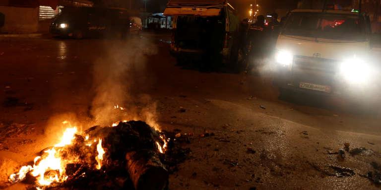 Des véhicules de police près d'un feu allumé par des manifestants, à Tunis, le 9janvier 2018.