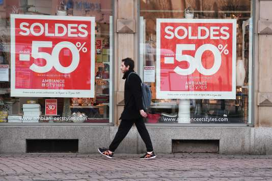 Un homme passe devant une vitrine proposant des soldes à Strasbourg, le 10 janvier.