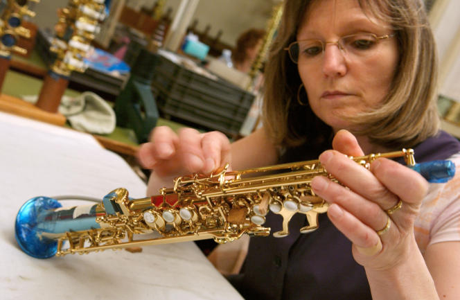 Une artisane contrôle les clés d'un saxophone à l'entreprise Selmer de Mantes-la-Ville (Yvelines), près de Paris, en avril 2005.