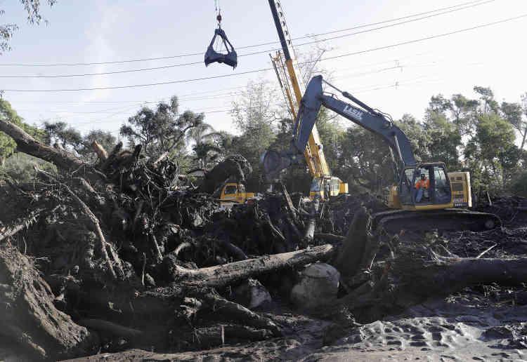 Une excavatrice enlève les débris d'une zone touchée, mercredi 10 janvier.