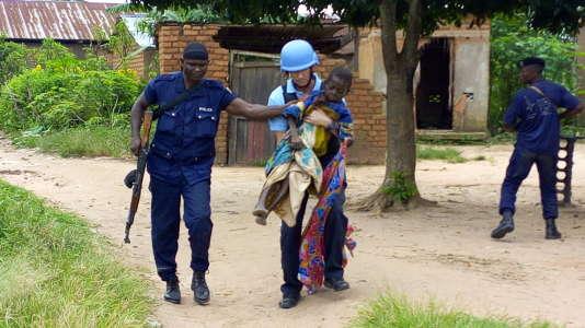 A Kananga, le 14 mars 2017, un casque bleu et un policier congolais évacuent une vielle femme qui a été frappée à coups de machette.