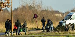 Migrants gather near a truck parking lot close to the N216 highway that leads to the ferry terminal, on January 12, 2018 in Calais. Asylum claims in France hit a record 100,000 last year, official figures shows early January, as the government draws up hotly-debated new legislation on immigration. / AFP / PHILIPPE HUGUEN