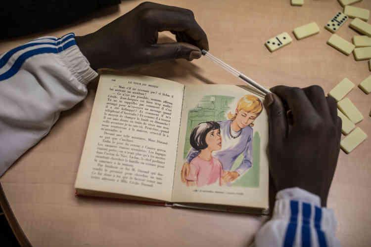 Un jeune migrant soudanais lit un livre en français. Des cours de français sont dispensés quotidiennement dans le centre.