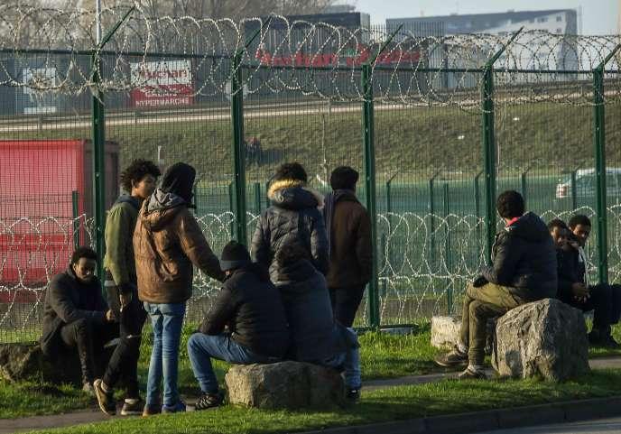 Des migrants attendent près d'un parking à camions, à Calais (Pas-de-Calais), le 12 janvier.