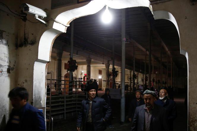 A Hotan (sud du Xinjiang), des Ouïgours sortent de la mosquée sous la surveillance de caméras, le 20 mars2017.