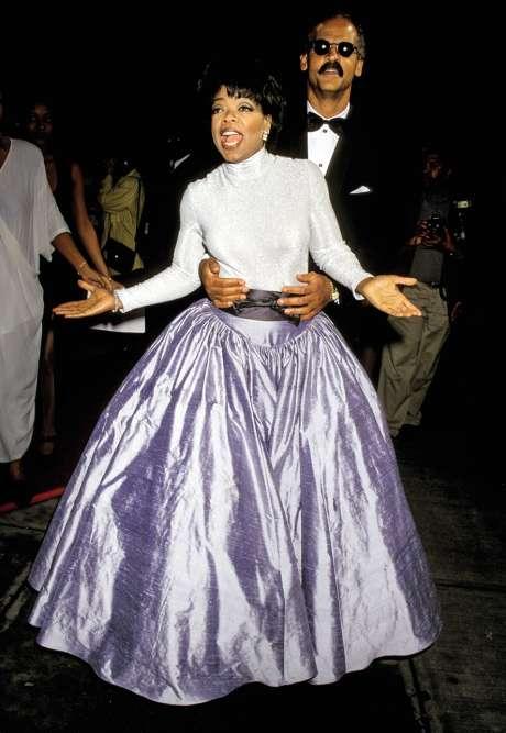 Deux ans plus tard, aux Essence Awards, Princesse Oprah tente de lancer le fameux « Ala queue leu leu » avec son compagnon Stedman Graham. Mais l'échec est cuisant. Ce qui a au moins le mérite de nous offrir une vue dégagée sur cette spectaculaire jupe, vraisemblablement maintenue par une cage en crinoline semblable à celle que les femmes de la haute, au début du XIXe siècle, portaient quand elles souhaitaient éblouir l'assemblée. D'où les lunettes de soleil de Stedman ?