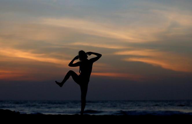 Femme faisant du yoga sur une plage à Colombo, Sri Lanka, 2018.