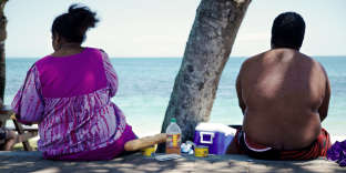 TO GO WITH AFP STORY BY CLAUDINE WERY People sit along the beach looking out at sea in Noumea on December 1, 2014. Obesity and diabetes are affecting citizens throughout the South Pacific islands, proportionately among the highest in the world, due to the change in eating habits and lifestyles as well as a genetic predisposition. AFP PHOTO/THEO ROUBY / AFP PHOTO / THEO ROUBY