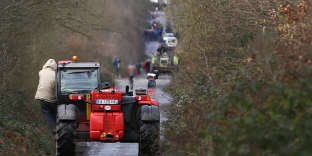 People clean the RD281 road in the zoned ZAD (Deferred Development Zone) in Notre-Dame-des-Landes, after the French government's official announcement to abandon the Grand Ouest Airport (AGO) project, near Nantes, France, January 22, 2018. REUTERS/Stephane Mahe