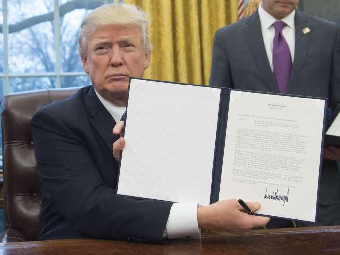 Le président américain Donald Trump brandit le décret mettant fin à la participation des Etats-Unis au traité de libre-échange transpacifique (TPP), le 23 janvier 2017 dans le bureau Ovale de la Maison Blanche à Washington.